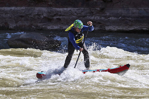 Clinton Johnson paddleboarding on rough waters
