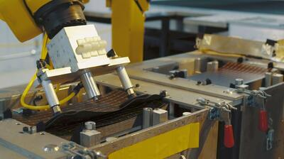 robotic arm picking up an amorphous silicon thin-film solar panel