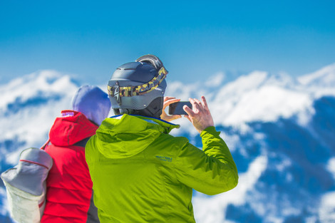 man taking a photo on top of a mountain